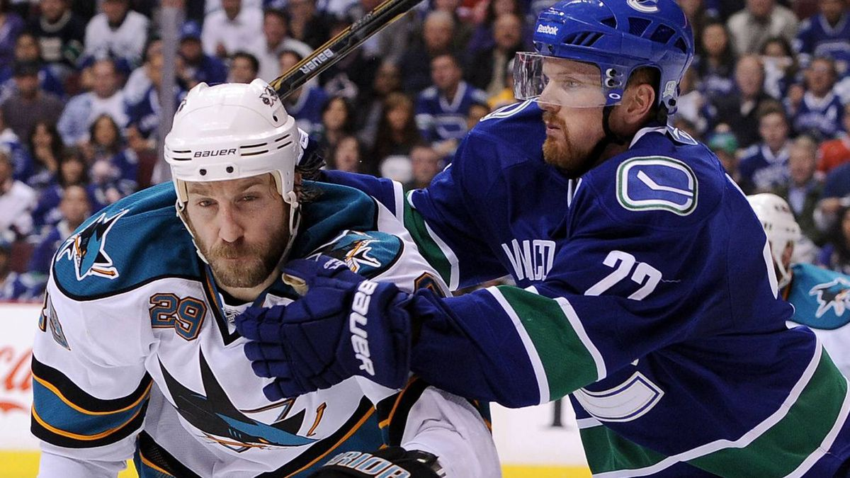 Ryane Clowe of the San Jose Sharks and Daniel Sedin of the Vancouver Canucks vie for position in the second period. (Photo by Harry How/Getty Images)