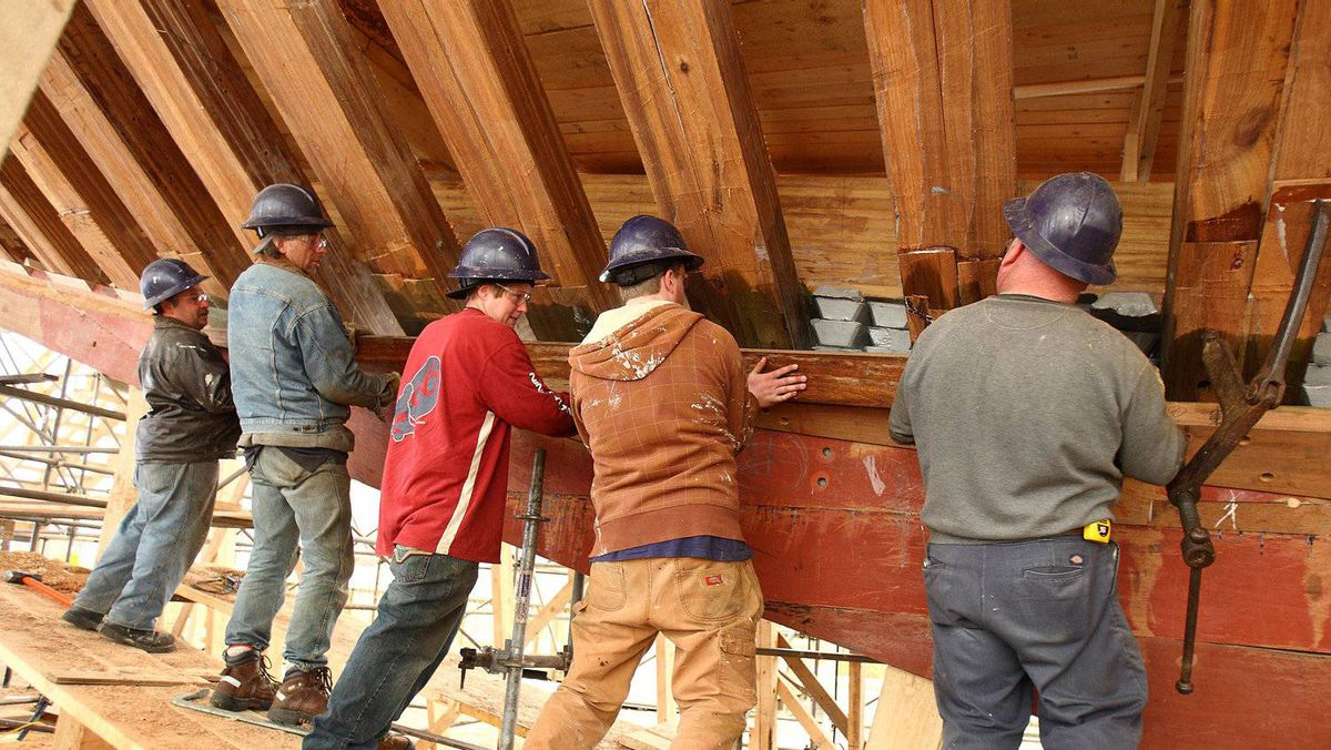 Planks of wood are bent with the help of steam and worked onto the hull while they are still warm, as this crew is shown doing.