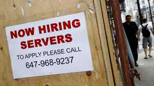 Pedestrians and shoppers walk past Now Hiring and a Join Our Team sign on various storefronts along Yonge Street in Toronto.