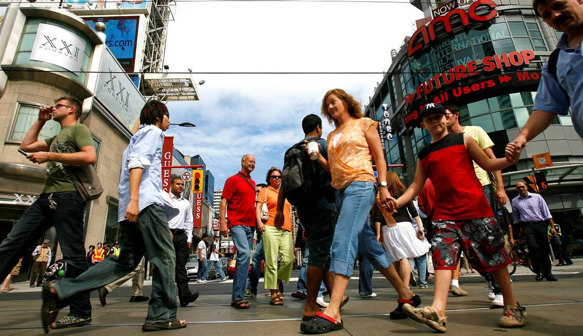 Pedestrians cross Yonge and Dundas streets in downtown Toronto.