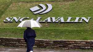 A pedestrian walks past the SNC-Lavalin Group Inc., headquarters in Montreal, May 7, 2009. SNC-Lavalin Group Inc reported a nearly 10 percent increase in first-quarter profit on Thursday, as the big Canadian engineering and construction company recorded larger gains from infrastructure concession investments such as toll roads. REUTERS/Christinne Muschi (CANADA BUSINESS)