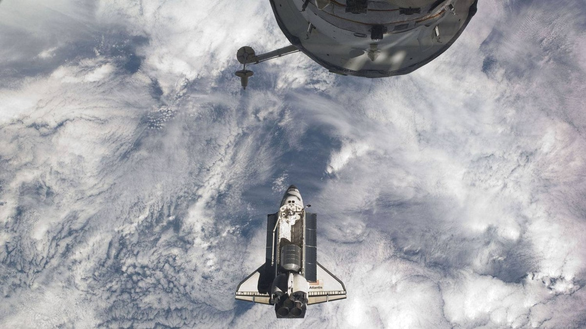 The space shuttle Atlantis is seen prior to docking with the International Space Station with part of a Russian Progress spacecraft docked to the station in the foreground on July 10, 2011.