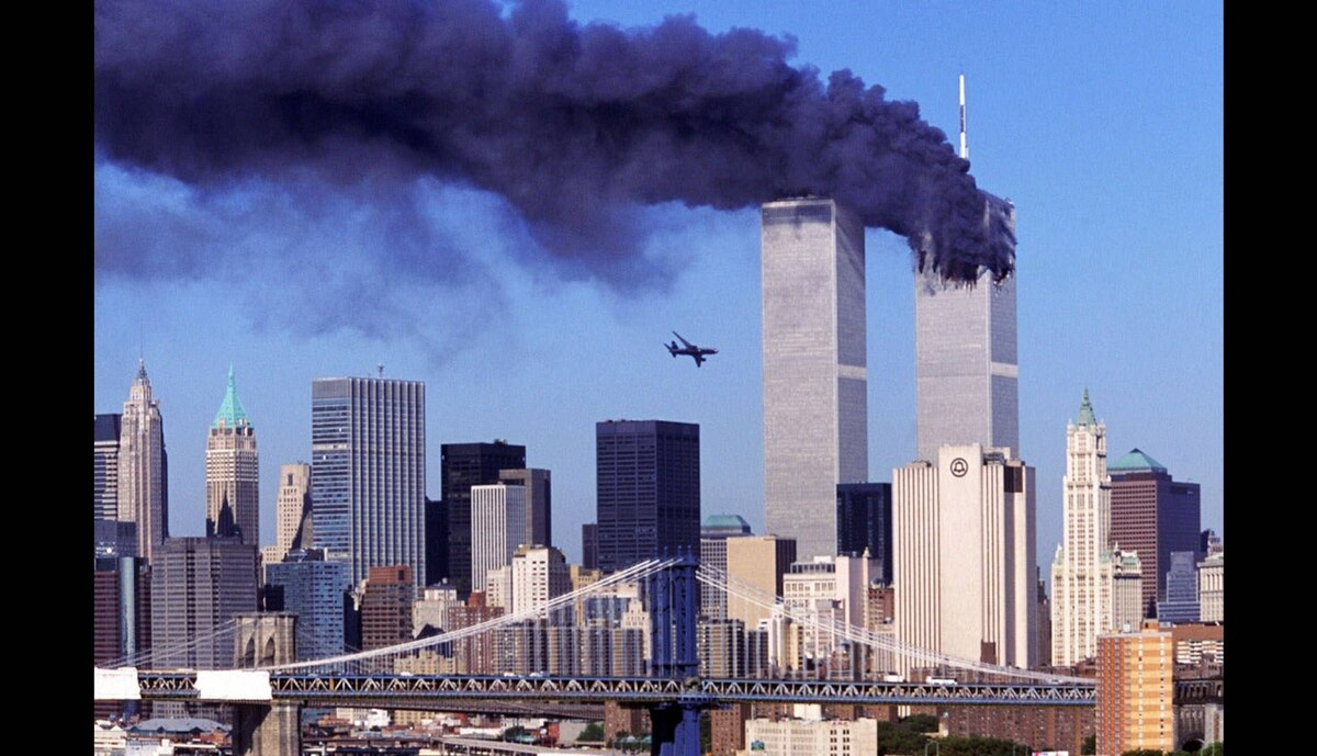 Hijacked United Airlines Flight 175, which departed from Boston en route for Los Angeles, is shown in a flight path for the South Tower of the World Trade Towers on Sept, 11, 2001. The North Tower burns after American Airlines Flight 11 crashed into the tower at 8:45 a.m.