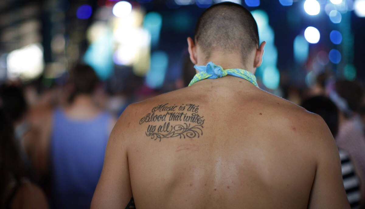 """A man with a tattoo that reads """" Music is the blood that unites us all"""" dances as Flux Pavilion and Doctor P plays at the 2012 Coachella Valley Music and Arts Festival in Indio, California."""