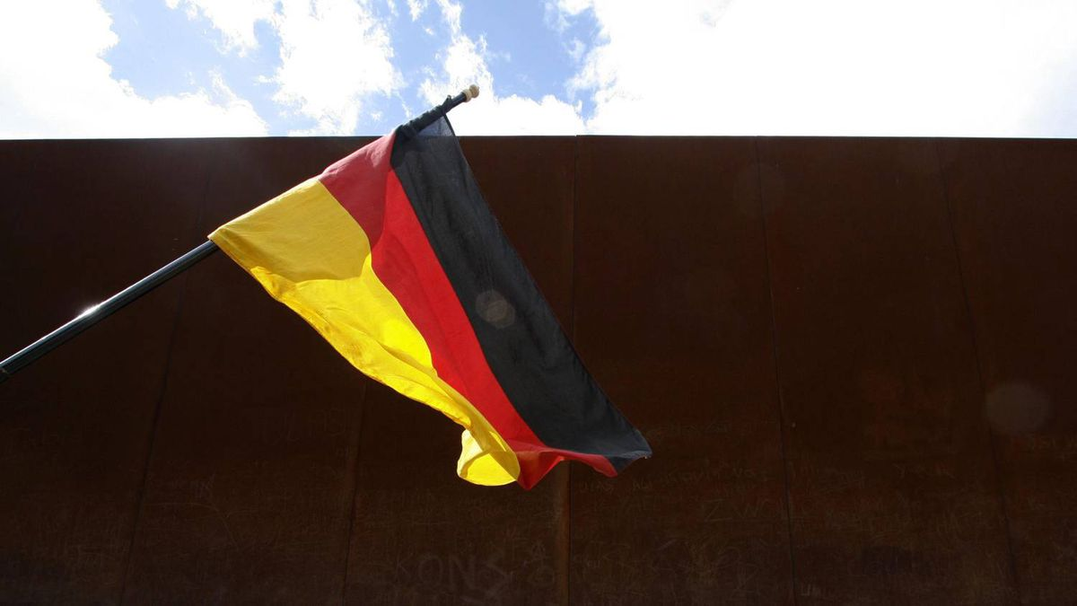 A German national flag waving in the wind, is pictured in front of a Berlin Wall memorial at Bernauer Strasse in Berlin, Aug. 13, 2008.