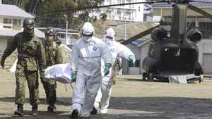 Self-defense force's members and others carry a resident who is suspected to be exposed to radiation, in Nihonmatsu, Fukushima, northern Japan Sunday, March 13, 2011 following radiation emanation from a nuclear reactor after Friday's catastrophic earthquake and tsunami.
