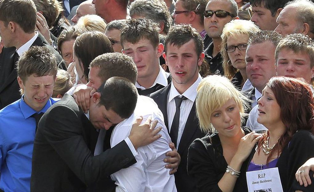 Friends of fallen serviceman Jimmy Backhouse react as his hearse passes mourners lining the street on July 14, 2009 in Wootton Bassett, England.