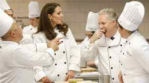 The Duchess of Cambridge looks on as Quebec Premier Jean Charest eats a hors d'oeuvres that she prepared during a visit to the Quebec Tourism and Hotel Institute in Montreal on Saturday, July 2, 2011.