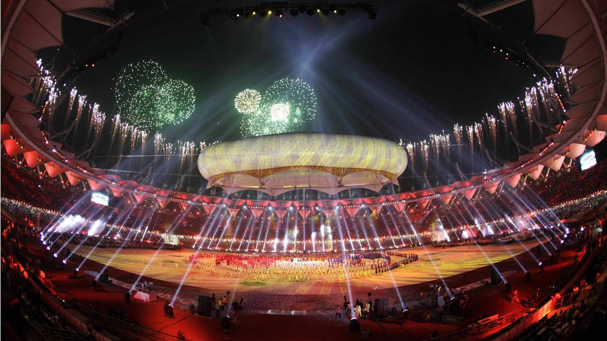 Lights are projected skywards over an aerostat as artists perform during the closing ceremony of the Commonwealth Games at the Jawaharlal Nehru Stadium in New Delhi, India.