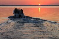 A speedboat on the water at sunset.