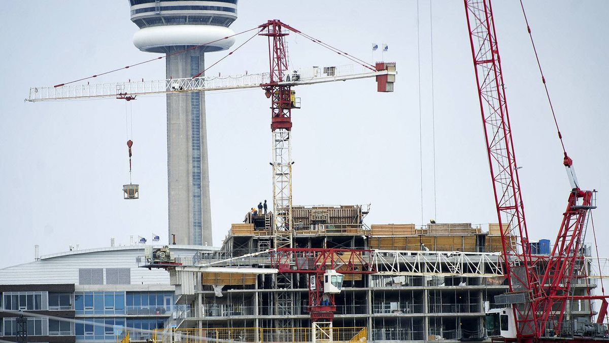 Workers are seen at a condo development in the west end of Toronto last month. CMHC estimates that roughly 25 per cent of condominiums in the Greater Toronto Area are sold but sitting vacant.