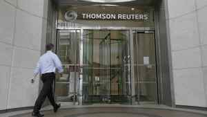 A worker enters the Thomson Reuters building in the Canary Wharf financial district of London August 6, 2009.