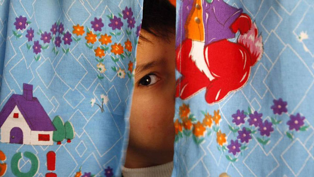 An autistic child peers from between curtains at the Consulting Centre for Autism in Amman, March 30, 2010.