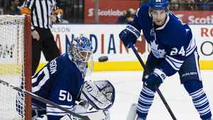 Toronto Maple Leafs goalie Jonas Gustavsson and John-Michael Liles, right, eye the puck as it passes the net during third period NHL action against the New York Rangers in Toronto on Saturday, March 24, 2012. THE CANADIAN PRESS/Aaron Vincent Elkaim
