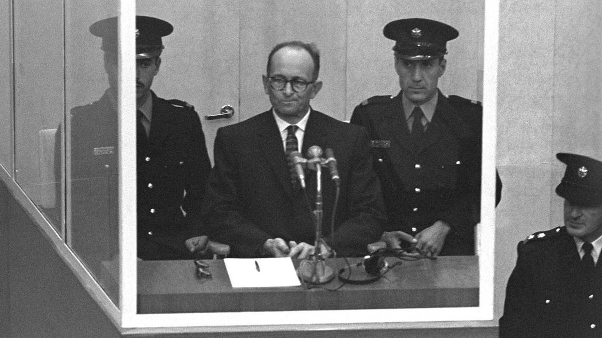Adolph Eichmann stands in a protective glass booth flanked by Israeli police during his trial on April 5, 1961 in Jerusalem.