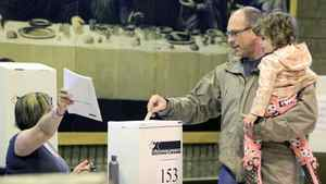 Under the watchful eye of his daughter, an Ottawa man casts his ballot in the federal election on May 2 , 2011.