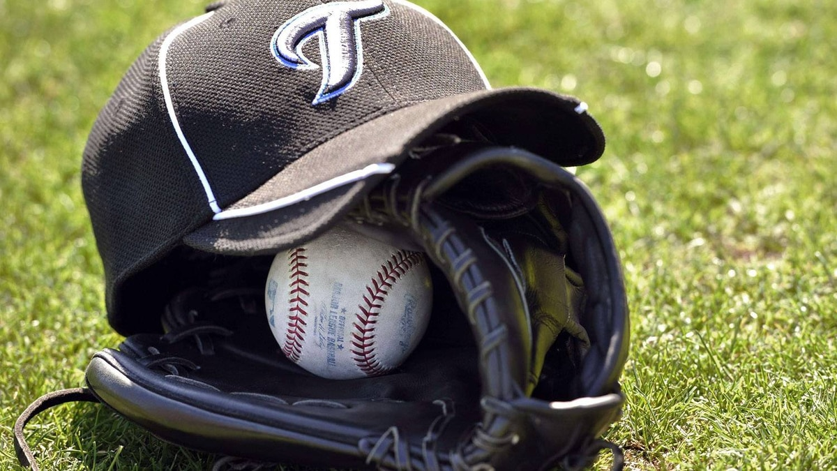 A Toronto Blue Jays players baseball cap, glove and ball sit on the grass during practice at their MLB American League spring training facility, in Dunedin Florida, February 13, 2011. REUTERS/ Mike Cassese