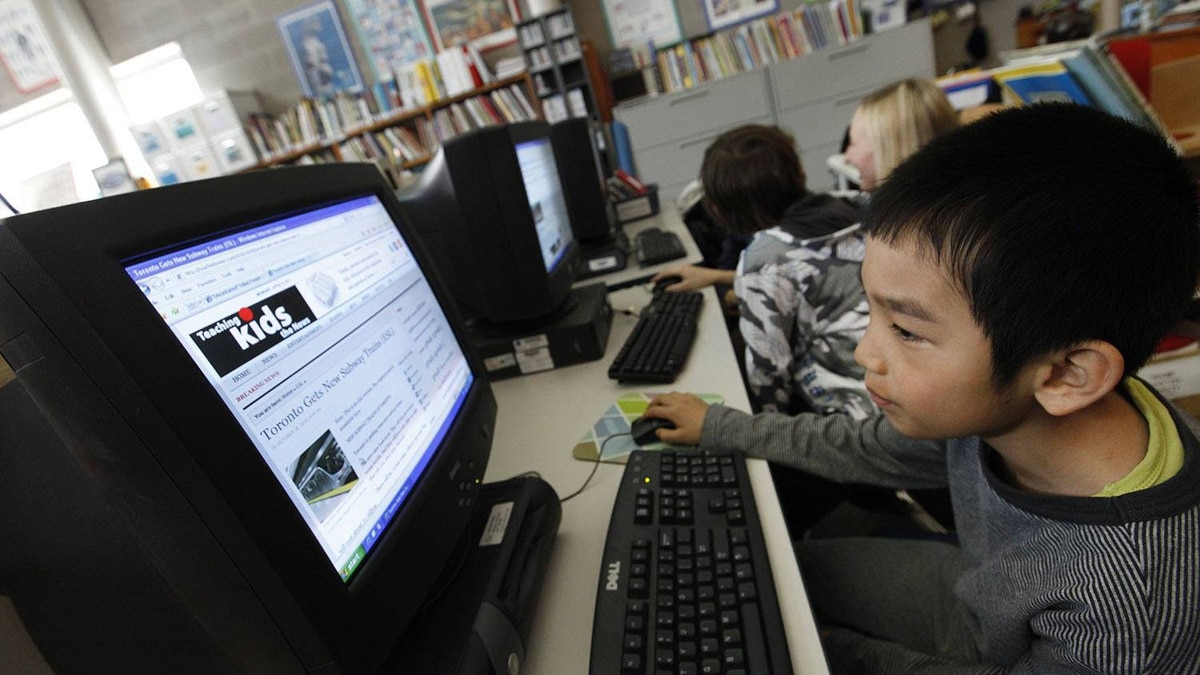Hao Chen Yu, 8 reads the news as one of the Teaching The Kids News developer, teacher Kathleen Tilly works with other students in the library at Eglinton Public School in Toronto.
