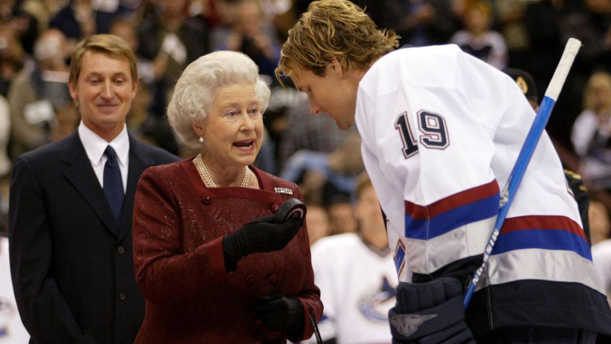 Queen Elizabeth II holds up the puck after it was presented back to her by Vancouver Canucks' captain Markus Naslund prior to a National Hockey League exhibition game between the Canucks and San Jose Sharks October 6, 2002. The Queen, who dropped the puck in an honorary faceoff, was given the puck back as a souvenir. Standing behind the Queen is Canadian hockey legend Wayne Gretzky.