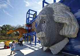 A girl looks at a large bust of Albert Einstein created out of lego bricks, displayed at Legoland Florida during its grand opening celebration in Winter Haven, Florida.