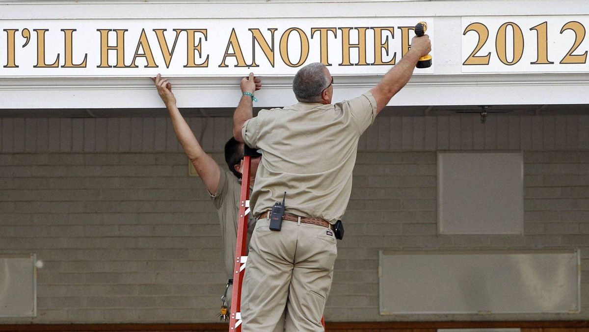 Workers put up a placard with the name I'll Have Another, winner of the 138th Kentucky Derby, at Churchill Downs in Louisville, Kentucky, May 5, 2012. REUTERS/Jeff Haynes
