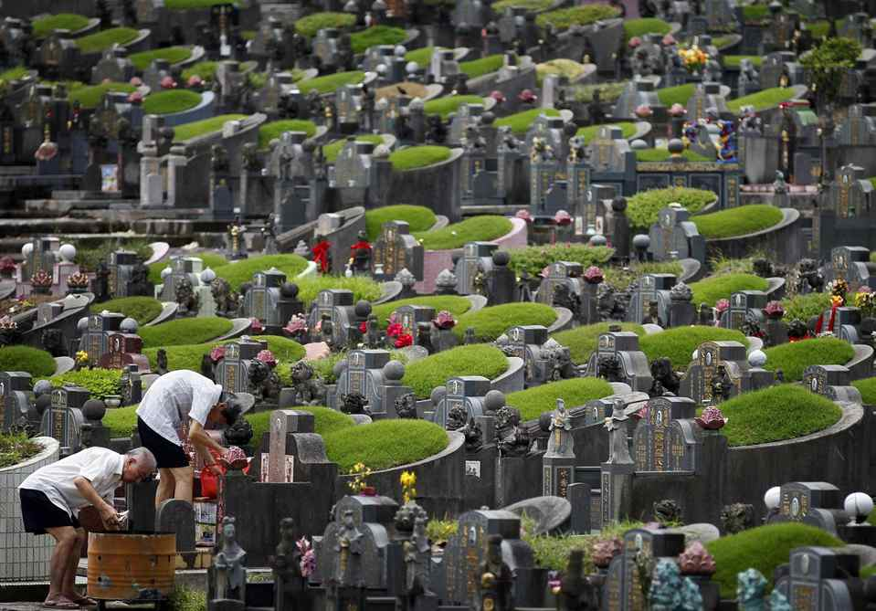 Two elderly men tend to a tomb at a Chinese cemetery during Qingming Festival, on Wednesday, April 4, 2012, in Singapore. Qingming, also known as Grave Sweeping Day, is a day on which Chinese honor the dead by cleaning family graves and burn offerings aimed at appeasing the dead in their afterlife.