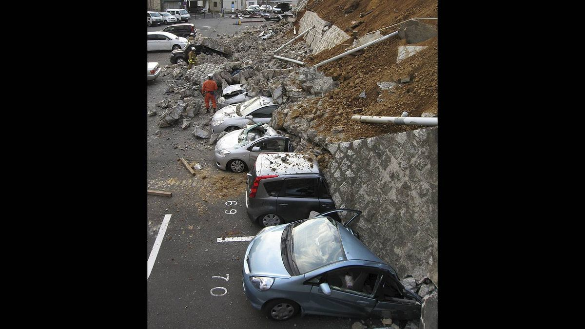 Vehicles are crushed by a collapsed wall at a carpark in Mito city in Ibaraki prefecture on March 11, 2011 after a massive earthquake rocked Japan.