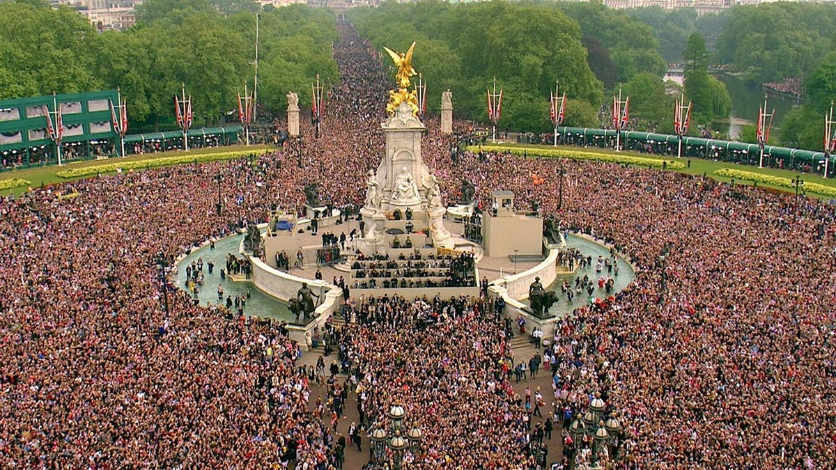 The crowd moves down the Mall, toward Buckingham Palace, to watch a kiss between Britain's Prince William and his wife Kate, the Dutchess of Cambridge, druring the Royal Wedding in London on Friday, April, 29, 2011.