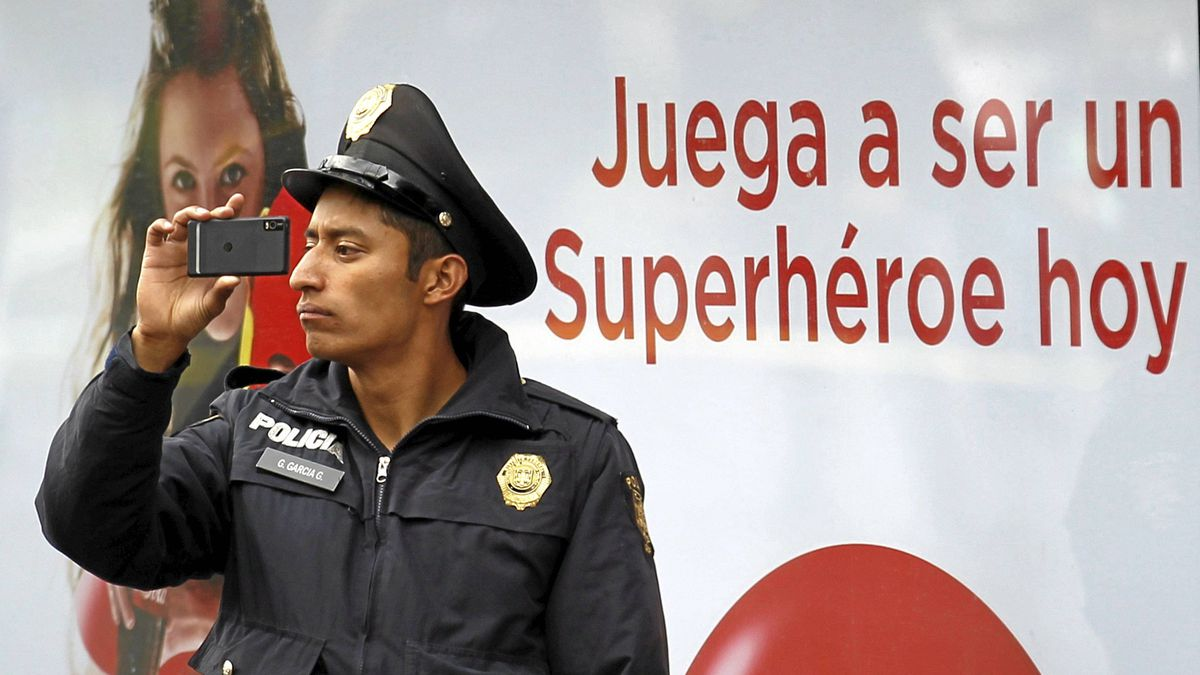 """A police officer takes photos with his cell phone during the """"Police in Mexico city, near to you"""" parade, organized by the Ministry of Public Safety to promote relations between the police and citizens, in Mexico city Jan. 15, 2012"""