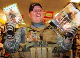 Erik Cota, dressed in fatigues, shows off his newly purchased copy of Call of Duty: Modern Warfare 2, early Tuesday in Redwood City, Calif.