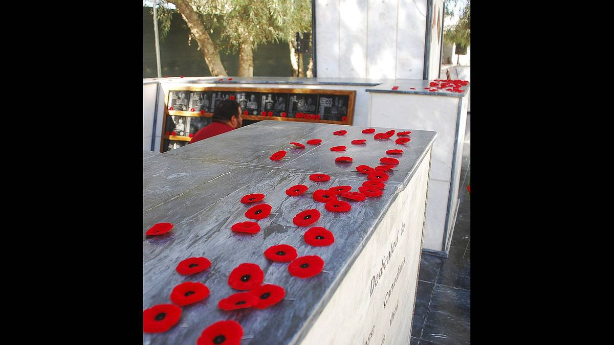Following a Remembrance Day ceremony at Kandahar Airfield, soldiers removed the poppies from their uniform and left them on a monument to Canadian soldiers killed in Afghanistan, on Nov. 11, 2010.