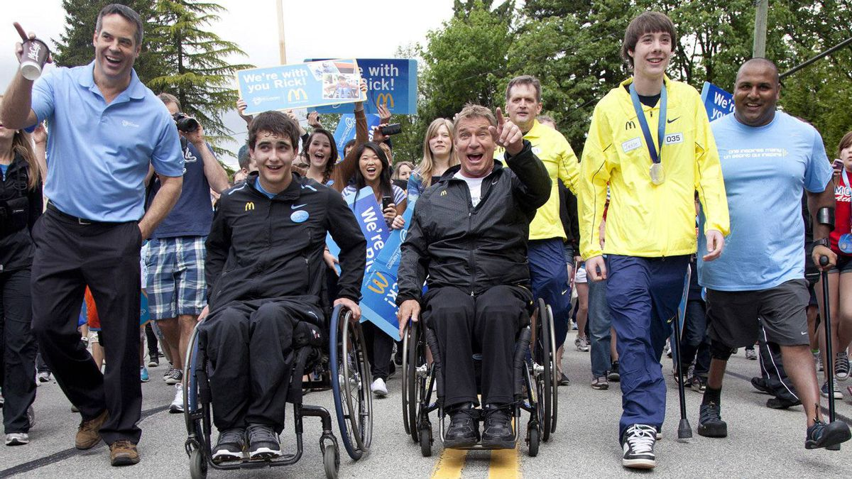 Rick Hansen, centre, smiles as he points to the top of a steep portion of the relay in Coquitlam, B.C. Friday, May 18, 2012. This years relay is the 25th Anniversary of Rick Hansen's Man In Motion World Tour and will wrap up in Vancouver on Tuesday.