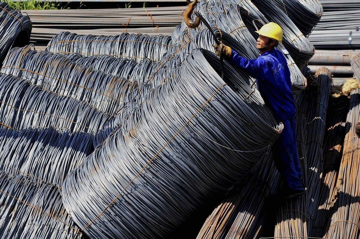 A labourer loads coils of steel wire at a steel market in Shenyang, Liaoning province.