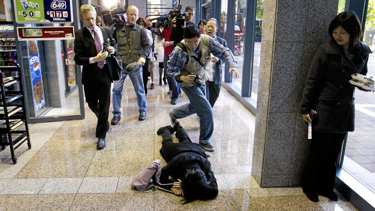 Van Thi Truong lies on the ground after colliding with a photographer as her husband, Langley mushroom farm owner Ha Quan Truong, centre right, reacts while leaving an inquest into the 2008 deaths on their farm, in Burnaby, B.C., on Wednesday.