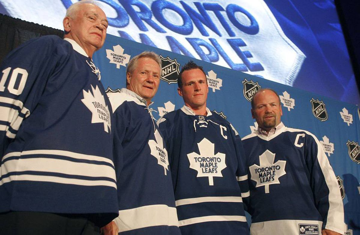 Toronto Maple Leafs new captain Dion Phaneuf, second from right, is flanked by former captains George Armstrong, Darryl Sittler and Wendel Clark, each wearing a jersey reflective of their era, during a news conference in Toronto.