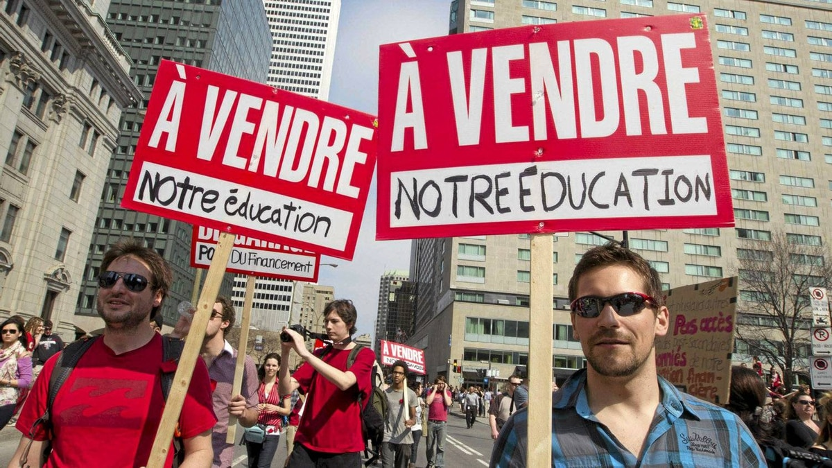 "Students hold signs during a protest against tuition hikes in downtown Montreal, Quebec March 22, 2012. The signs read ""For sale our education""."