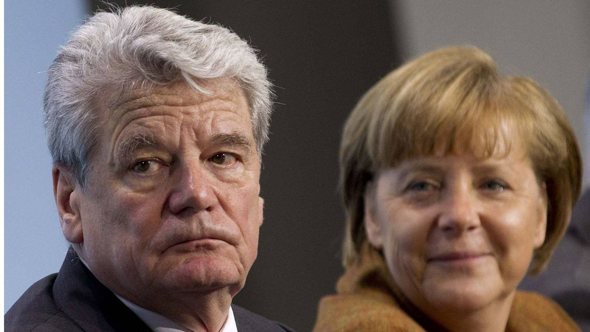 German Chancellor Angela Merkel (R) looks at former East German rights activist Joachim Gauck, joint candidate of government and opposition for the post of president, at the Chancellery in Berlin Feb. 19, 2012.