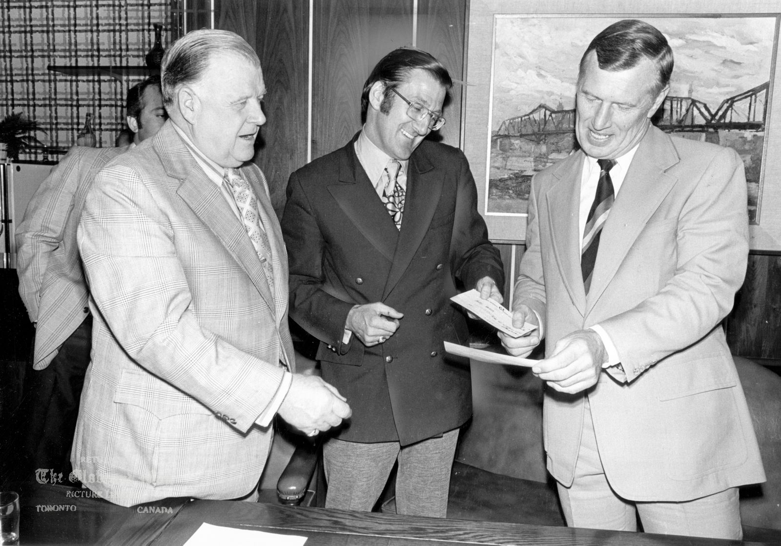 The notes transcribed from the back of this photograph are as follows: JUNE 26, 1972 -- CANADA-RUSSIA HOCKEY SERIES TV RIGHTS -- Harold Ballard, left, and Alan Eagleson, centre, each hand over $100,000 cheques to Allan Scott, business manager of Hockey Canada on June 26, 1972 in Toronto as down payment for the $750,000 television rights for the Canada-Russia Summit Series due to begin Sept. 2, 1972. Photo by Tibor Kolley / The Globe and Mail Originally published June 27, 1972. Summit Series