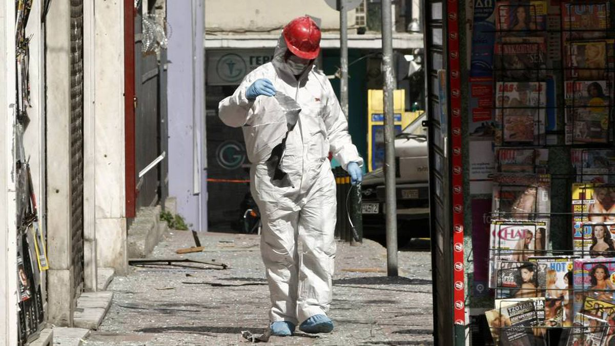 A police investigator carries a piece of debris after a bomb explosion outside the offices of a far-right group in Athens March 19, 2010.
