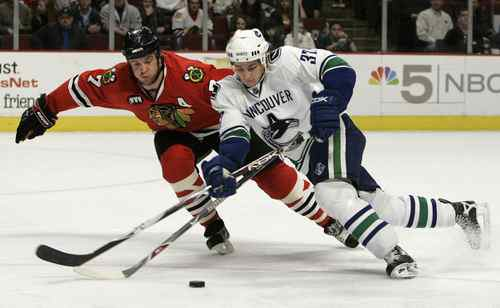 Vancouver Canucks center Rick Rypien battles Chicago Blackhawks defenseman Brent Seabrook for the puck in the second period of their NHL hockey game in Chicago, March 2, 2008.
