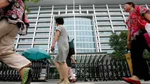 Shoppers walk past the headquarters of the Industrial and Commercial Bank of China in Beijing Wednesday July 19, 2006.