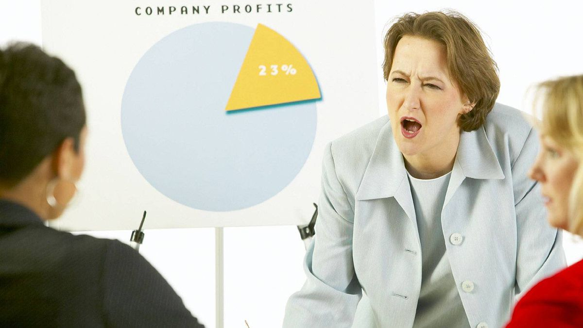 Agitated businesswoman in meeting with coworkers.