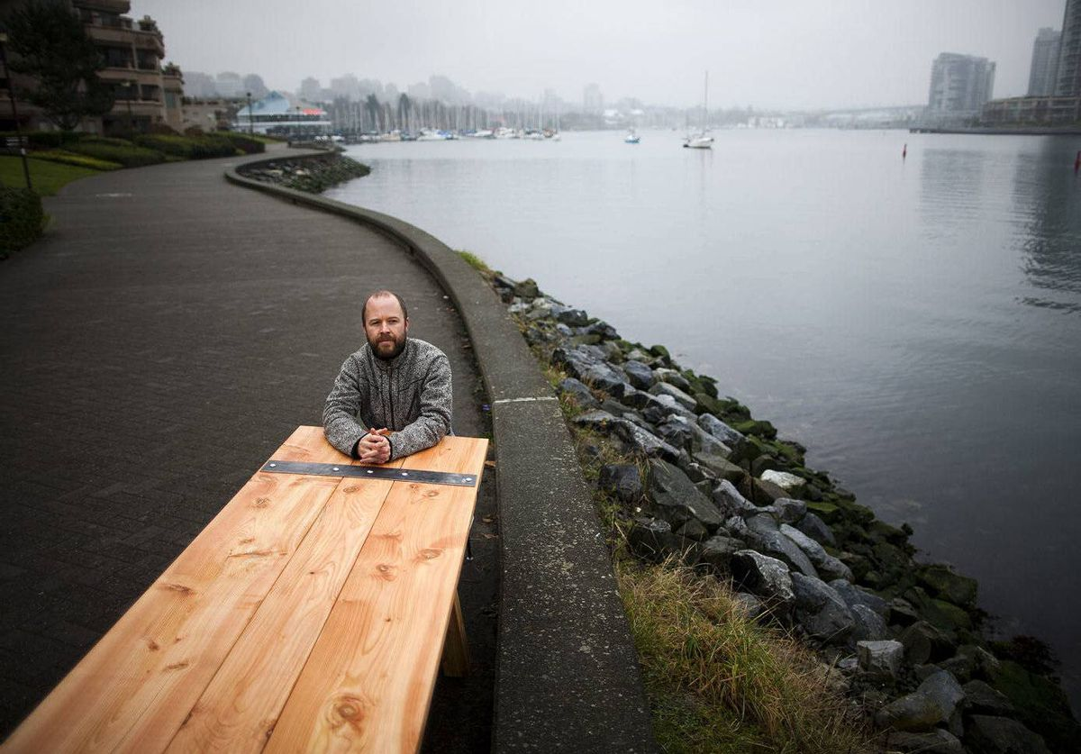 University of British Columbia grad student, Josh Welch, sits at a section of a 30-foot table in Vancouver, British Columbia. The table will be placed in different neighbourhoods and people invited to sit down and talk about sustainability.