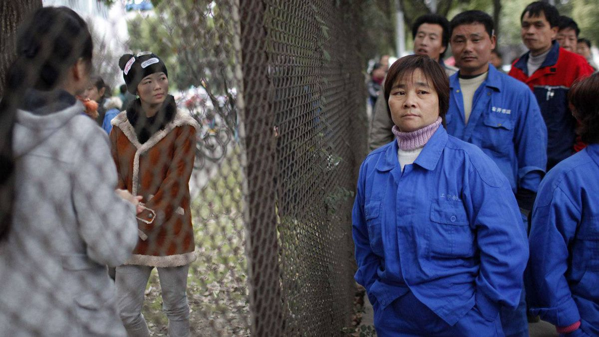 Striking workers from Hi-P International in suburban Shanghai stand next to a fence. Chinese police detained around a dozen workers at the Singapore-owned electronics plant on Tuesday.