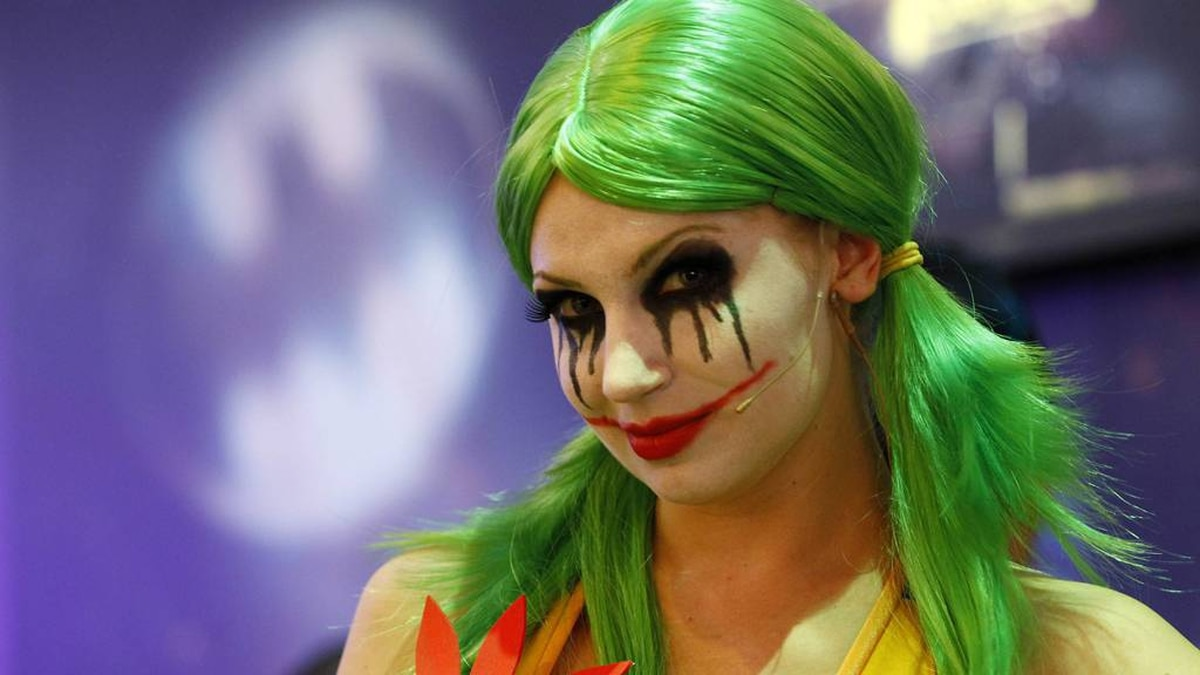 """A woman dressed as the character """"The Joker"""" smiles for the camera while promoting Warner Bros. Interactive Entertainment, Inc.'s new video game """"Gotham City Impostors"""" during the Electronic Entertainment Expo or E3 in Los Angeles June 8, 2011."""