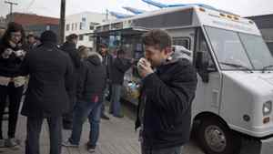 Alessandro Vianello eats a Bulgogi Burrito at lunch time as other customers line up at the Coma Food Truck in Vancouver, Thursday, March 8, 2012. The popular Vancouver food truck did not receive its renewal permit this year and it is shutting down Saturday.