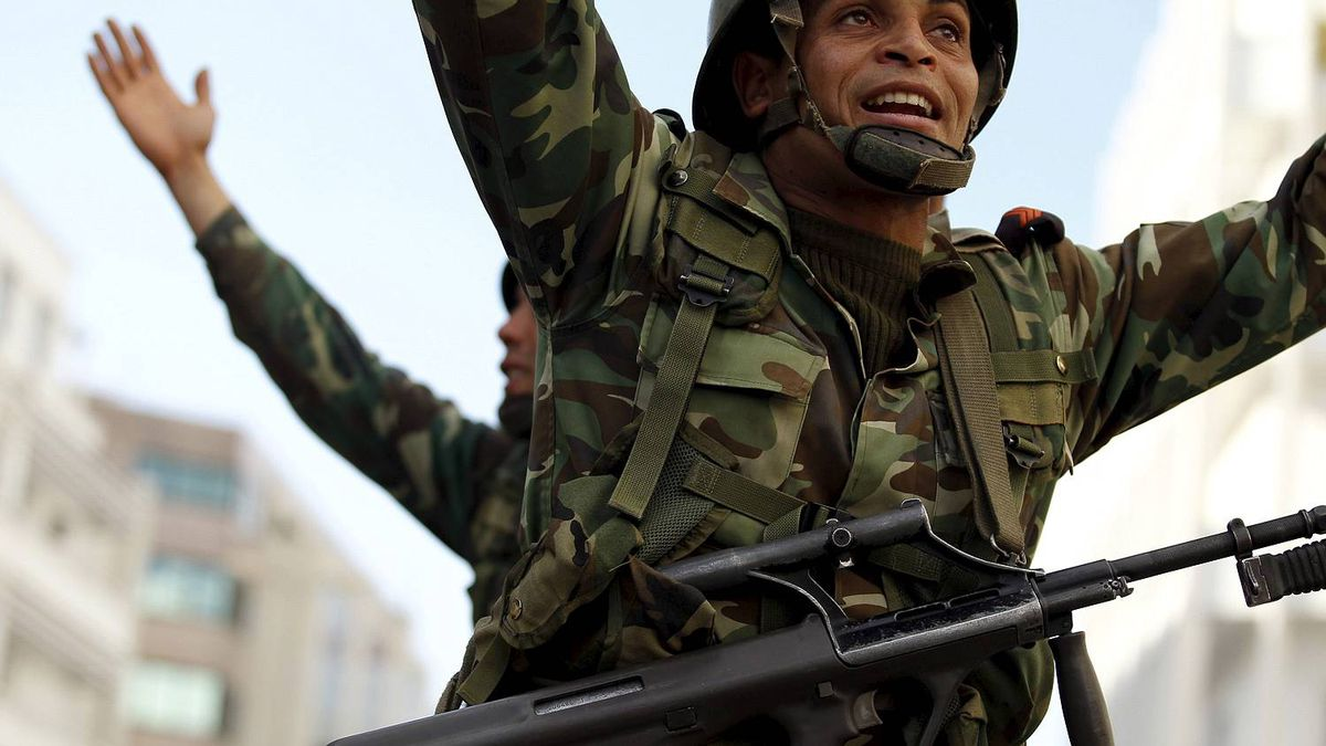 Tunisian soldiers try to calm down rioters during clashes with the police in downtown of the capital Tunis