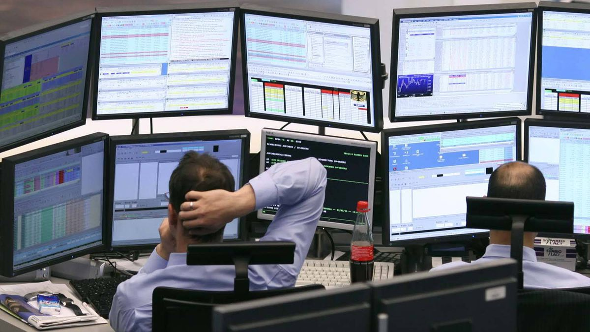 A trader scratches his head as he watches his screens on the trading floor of Frankfurt stock exchange