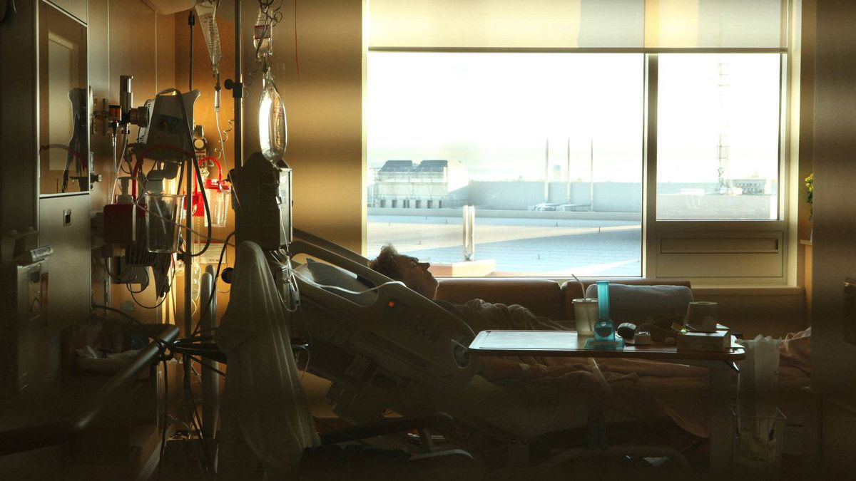 A patient rests from her room with bright windows with a view, that partially open for fresh air and large signage for easy access at the Patient Care Centre in Victoria, B.C.