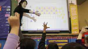 Monica Fong from David Livingstone Elementary works on a SMART board in class in Vancouver, BC. The touch-sensitive display connects computer, digital projector and students to show computer image and work.